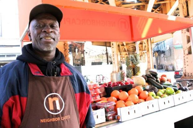 "Neighbor Cart vendor Anthony Weston sells fresh, uncut fruit at a moveable stand in front of the Damen Blue Line ""L"" stop in Wicker Park."