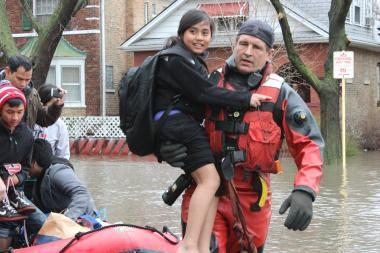 An evacuee gets a lift from the Chicago Fire Department during Thursday's flooding.