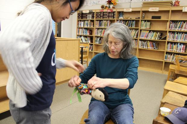 Leslie Travis, the librarian at Ray Elementary School, is powering the sewing machine for her afterschool club with bicycle-generated electricity.