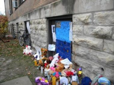 A shrine for a murder victim is filled with stuffed animals and posters.