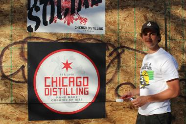 Chicago Distilling Company owner Jay DiPrizio puts up posters for the distillery he founded with his wife and brother. It's set to open at the end of the month with a public tasting room opening in July.