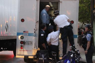 Police officers arrest one young man and place him in the back of a police wagon.