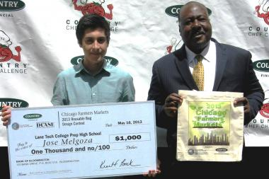 Jose Melgoza (l), a junior at Lane Tech, won the annual contest to design a reusable tote bag for the city's farmers markets. Mike Fisher, vice-president of market development at Country Financial, presented Melgoza with a $1,000 check.