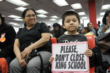 A boy holds a sign at a King Elementary school closure meeting on April 11. On Sunday, Hearing Officer Bernetta Bush recommended the school be kept open.