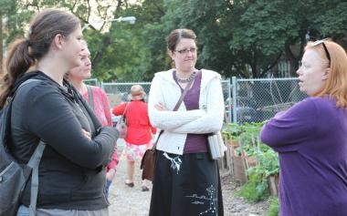 "Shylo Bisnett (left) and members of Albany Park Neighbors held their June meeting at Global Garden community garden. Plans were discussed for a ""positive loitering"" night later in the month."