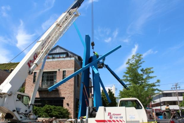 Chevron, the big blue statue along Armitage at Burling, was being taken down Tuesday afternoon, but only temporarily so the owner can move the statue back five feet.