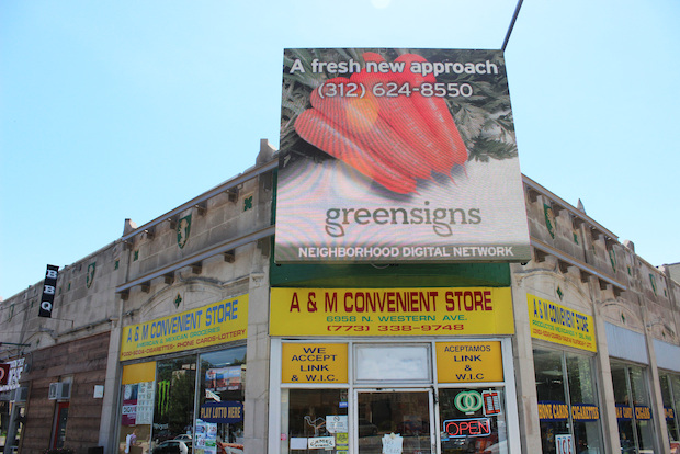 "Neighbors say a digital billboard erected above the storefront of a convenience store earlier this month at Western and Lunt avenues is ""ugly"" and ""hideous."""