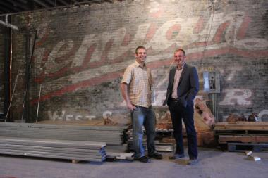 Nathan Sears (l.) and Adam Hebert, owners of The Radler, stand in front of a Bohemian beer ad they found behind drywall as they prepared the space for their new project, a Bavarian beer hall and restaurant.