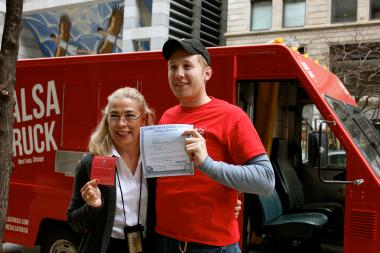 Rosemary Krimbel, the city's chief of Business Affairs and Consumer Protection, presents Dan Salls with a license to cook food on his Salsa Truck, the first in the city so honored.