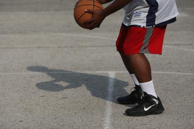 A teenager plays basketball in Garfield Park.