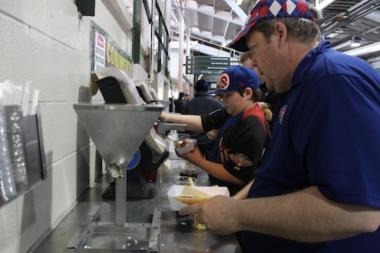 Beneath the bleachers at Wrigley Field, fans adorn their hot dogs with onions and mustard on Opening Day in April.