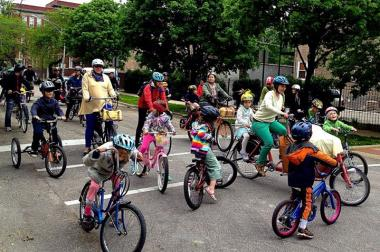 A group of parents and children ride during a Kidical Mass ride in Logan Square in May.