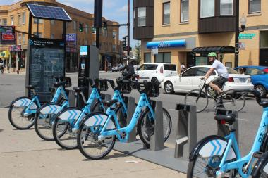 A bicyclist rides past a Divvy bike rental station in Logan Square. Scott Wastyn of Oscar Wastyn Cycles wonders how many people will use it in a neighborhood where many already own bikes.