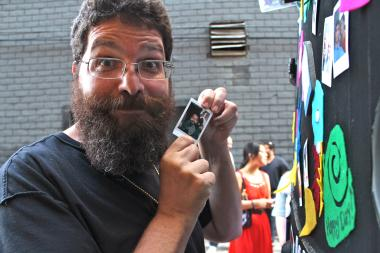 "Block X resident Moshe Tamssot holds up a Polaroid picture of himself while posing next to the Make With Moto van, a traveling display of 3-D printers. The printers are just one type of technology Tammsot hopes to bring to ward residents via a ""Makers"" space he hopes to open at 1140 W. Madison St."