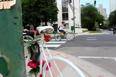 A bicyclist rides past a Ghost Bike memorializing Neill Townsend, who was struck and killed by a truck on Wells Street just south of Oak Street in October.