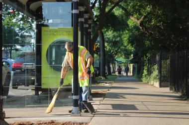 A Streets and Sanitation worker cleans up broken glass from a bus stop in the 4500 block of North Sheridan Road.