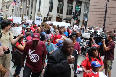 Jitu Brown and 9-year-old Garvey Elementary student Asean Johnson (foreground) lead marchers down LaSalle Street from CPS Headquarters to City Hall Wednesday.