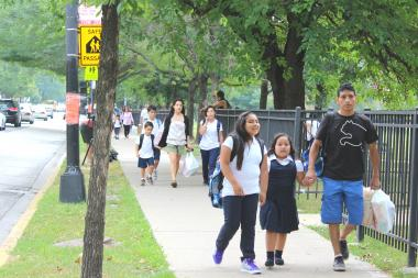 A steady stream of Chappell students make their way up Foster Avenue along a safe passage route.
