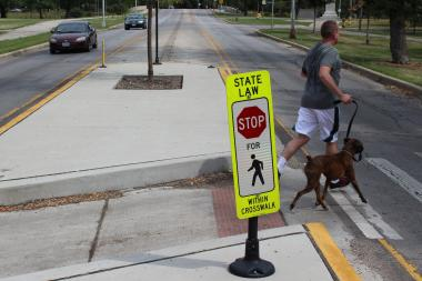 A man walking his dog trots through a crosswalk as traffic breezes by in Humboldt Park. Speed cameras to be installed in the area next month are expected to slow traffic.