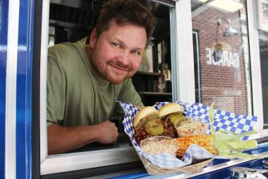 Joey Woodel, owner of Husky Hog BBQ, serves up pulled-pork sandwiches and sweet spring corn from his food truck.