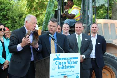 Flanked by union leaders and city water officials, Gov. Pat Quinn holds up a portion of an aged water pipe in need of repair.
