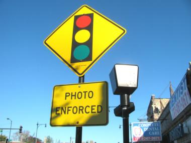 A sign warns drivers of the red-light camera at Irving Park Road and Kedzie Avenue.