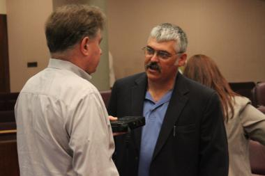The NRA's Todd Vandermyde talks with a reporter before Friday's Finance Committee meeting.