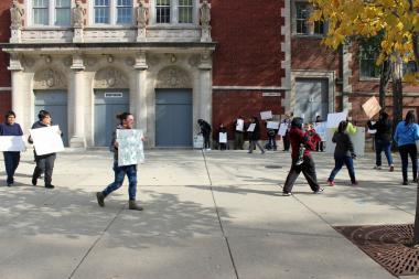 Protesters march in front of the Marine Math and Science Academy in 2013 before an announcement from officials that the military high school would move to the Ames Middle School building.