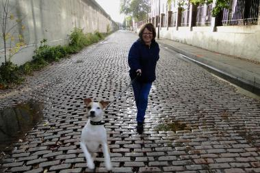Mary Drogus with her daughter's dog, Scooter, walks on Bloomingdale Avenue, just west of Hermitage Avenue in Bucktown.  The brick street will be replaced with asphalt next fall.