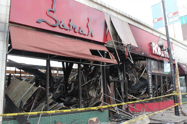 Crews began demolition Saturday on the building housing three businesses ruined in Friday night's fire.