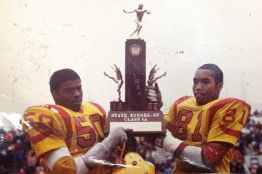 Robeson High School football players Tiffany Lee (50) and Vince Tolbert (81) hold up the IHSA Class 5A State Runner-up trophy after a 16-12 loss to Rockford Guilford in the 1982 state championship game.