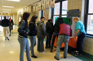 The Ames Middle School Local School Council set up voting booths Tuesday and invited parents to vote on whether they wanted a military school there.