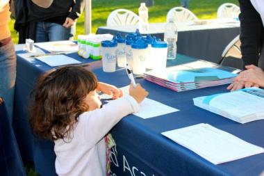 A toddler signs herself up for GEMS World Academy at an informational expo hosted by the school in October.