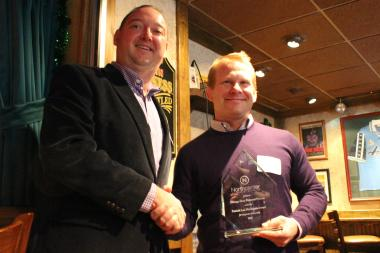 Garrett FitzGerald (l), Northcenter Chamber of Commerce executive director, presents Wade Anderson of Orange Shoe Fitness with the PLM Corporate Citizenship Award.