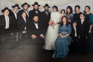 Rabbi Baruch Hertz (top row, fourth from left) poses for a photo with his family, which includes 11 children, during the wedding of one of his daughters.
