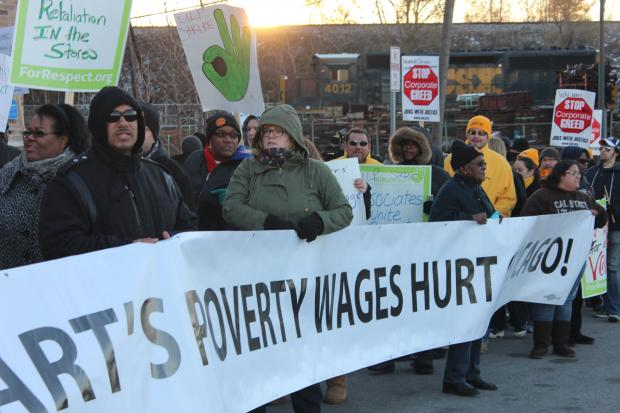 About 100 Wal-Mart employees protested Wednesday on the South Side demanding that full-time employees be paid an annual salary of at least $25,000.