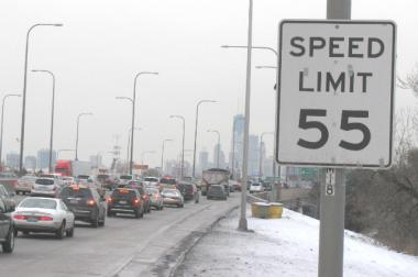 Cars on the inbound Kennedy Expressway cruise by a 55 mph speed limit sign on their way into the city.