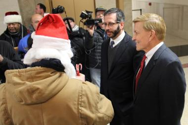 Aldermen John Arena and Bob Fioretti (r.) receive candy canes from City Hall protesters Monday.
