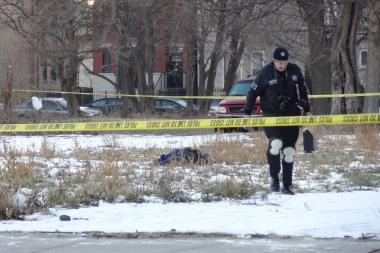 Police investigate the scene where a 23-year-old man was shot to death near 45th Street and Indiana Avenue.
