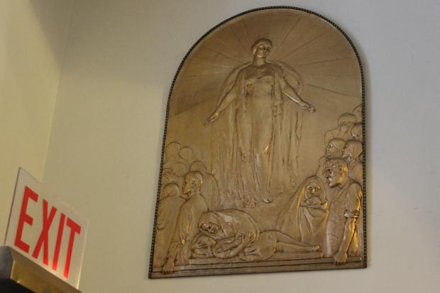 Lorado Taft's bronze bas-relief tablet commemorating the Iroquois Theater fire is tucked away in a corner of the City Hall lobby above a revolving door.