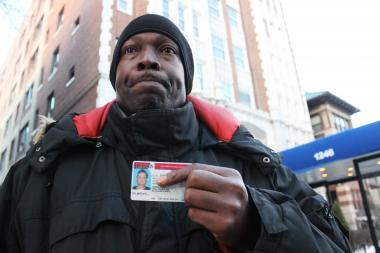 James Barnett holds the driver's license of Charles Roth, 55, outside Astor House in Rogers Park. Barnett cared for Roth, who died Wednesday, before they were both evicted Friday from the Astor House.