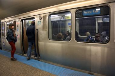 Commuters get on a train at the Logan Square Blue Line station