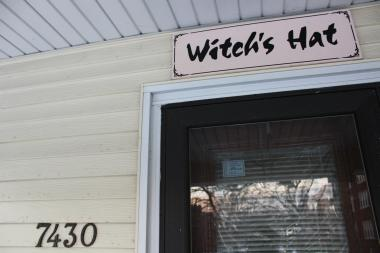 "The ""Witch's Hat"" sign above the home's front door"