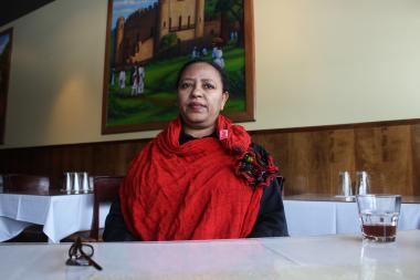Ethiopian Diamond owner Almaz Yigizaw first opened the restaurant in 1996 after emigrating from Gondar, Ethiopia, her hometown, which is depicted in the painting on the wall behind her.