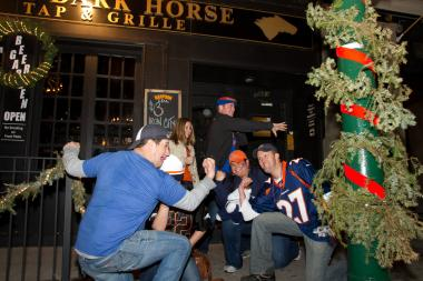 "Members of the Chicago Bronco Nation perform a ""Tebow"" in front of a Pittsburgh Steelers-friendly bar after former Broncos quarterback Tim Tebow's touchdown pass beat the Steelers in overtime in a 2012 playoff game."