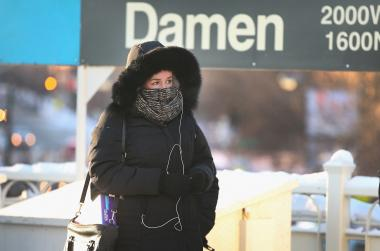 "A woman waits at the Damen Avenue ""L"" stop Tuesday."