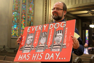 Craig Cleve of the Chicago Teachers Union displays a poster before the start of Tuesday's protest.