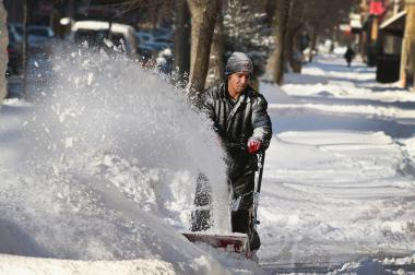 The National Weather Service issued a winter storm warning for 9 p.m. Friday to 6 p.m. Saturday. Earlier this month, Felix Santos cleared snow from a sidewalk in the Humboldt Park neighborhood.