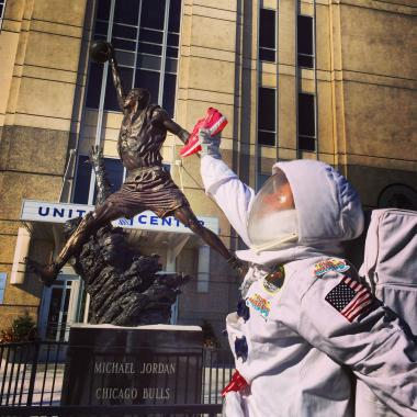 "The ""Transcendronaut"" poses in front of the Michael Jordan statue."