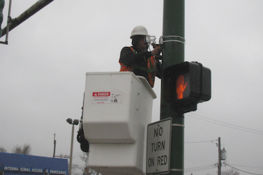 Contractors for Xerox install new red light cameras at the intersection of Diversey and California.
